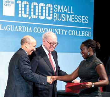 Goldman Sachs chairman/CEO Lloyd Blankfein, left, and Warren Buffet congratulate graduate Saudia Davis.