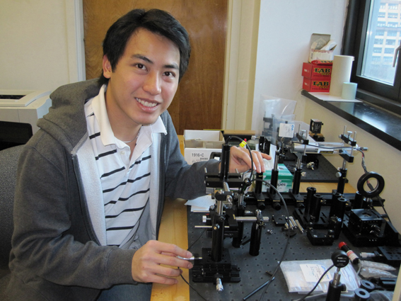 City Tech student Thinh L with the apparatus he built to measure the optical transmission of meteorite samples.