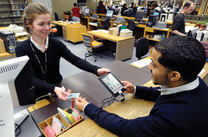 Addy Soto, above, head access services librarian at Lehman College Leonard Lief Library, checks out a Sony Reader to Joel Lopez, a graduate student in special education.