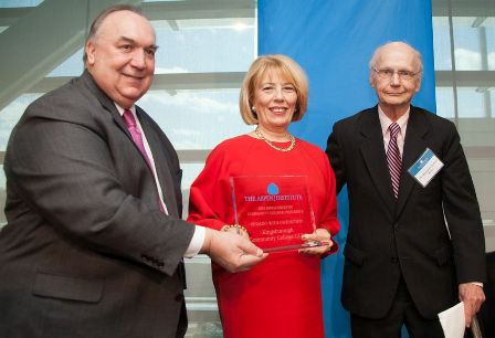 Kingsborough Community College President Regina Peruggi accepts Aspen Prize for Community College Excellence. The award is presented by John Engler (left) and Richard Riley (right), members of the Prize Jury.