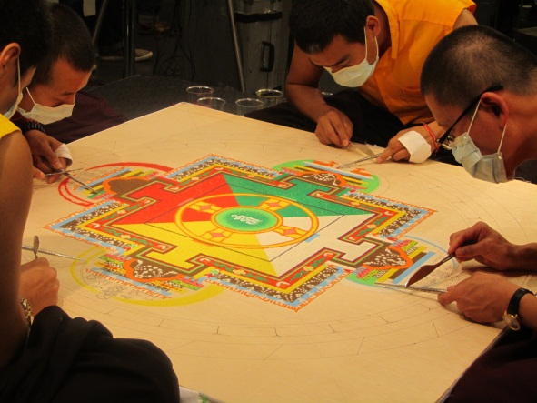 Tibetan monks create a sand mandala using colored sand.