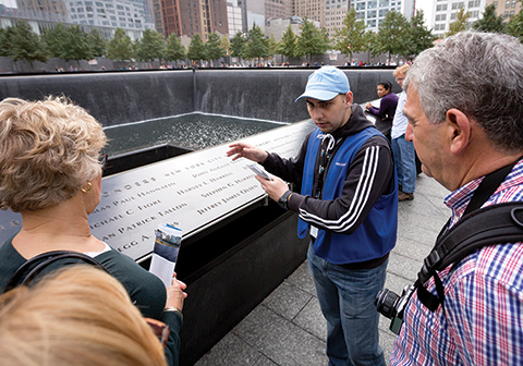 Andrei Stump, a CUNY Service Corps student, guides visitors at the 9/11 Memorial site.