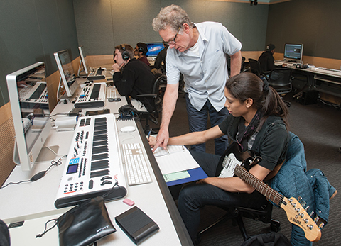 Michael Bacon teaching film scoring at Lehman College. He works with student Nicole Johnson.
