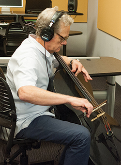 Michael Bacon plays the cello, his first instrument, in Lehman's Multimedia Center.