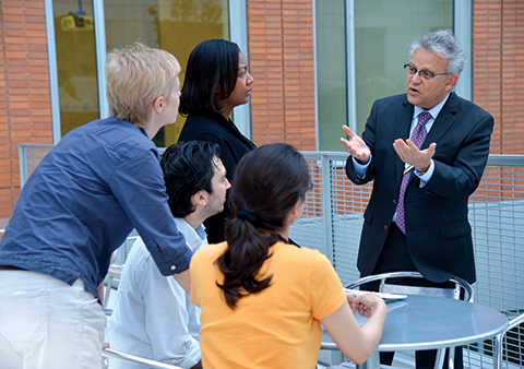 Dr. Ayman El-Mohandes, dean of the CUNY School of Public Health, chats with students on the school's terrace.
