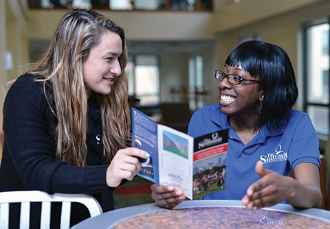 Isioma Ononye, a Queens College junior and a courtesy desk attendant at Summit Apartments, chats with Anastasia Shakalis, another Queens College junior.