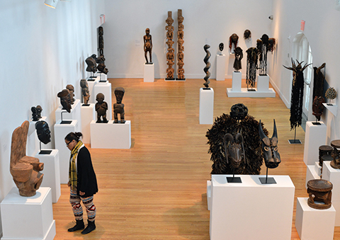 The Powerful Arts of Cameroon at QCC's Art Gallery. At left, Veronica Chin Hing, a Brooklyn College student, at right, Eric Vehstedt of Queensborough Community College viewing the display.