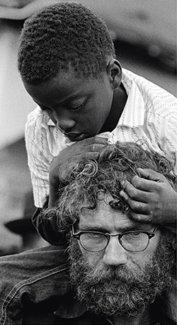 A young marcher rides atop the shoulders of another older protester in the 1965 civil rights march from Selma to Montgomery, Ala.