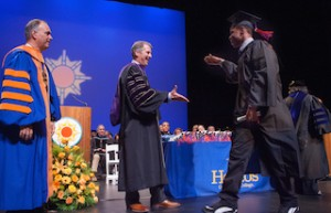 Chancellor James B. Milliken congratulates a graduate at Hostos Community College commencement exercises on June 3.  Hostos President Felix V. Matos Rodriguez is at left.