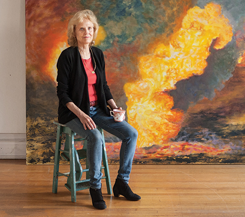 "Susan Crile at her studio in Manhattan with her oil painting ""Aflame"" in the background. The painting is one of the works from her ""Fires of War"" series, based on the burning oil fields of Kuwait."