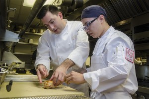 Chef Aaron Bludorn and Christian Bolanos work together in the kitchen at Cafe Boulud. Credit: A. Vargas