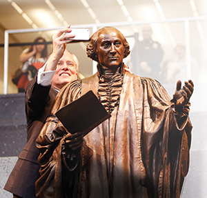 John Jay College President Travis takes a 'selfie' with the unveiled statue of the college namesake.