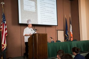 Photo of Chef Mark D'Alessandro, director of KCC's Culinary Arts program addressing attendees at Coast Guard meeting