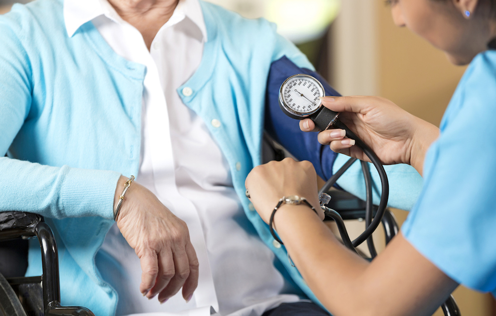 Senior woman in wheelchair getting her blood pressure taken