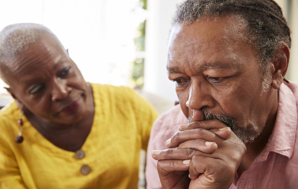elderly man looking pensive while elderly woman looks on