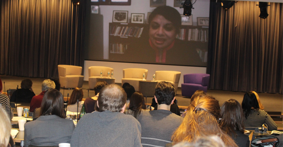 Audience members listen to a video message from Radhika Coomaraswamy