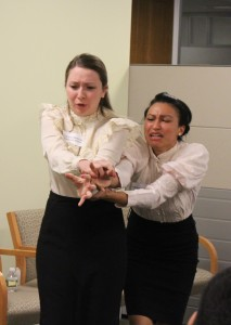 """Student actors from Brooklyn College reenact a scene when workers could not escape the 1911 Triangle Shirtwaist fire because the doors were locked """"against the law"""" from the outside."""