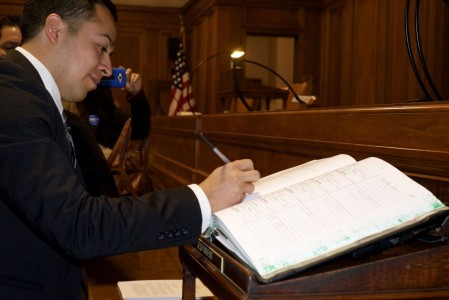Cesar Vargas ('11) signs the roll of attorneys, after taking the oath.