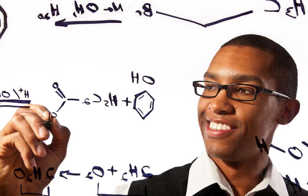 Man in glasses smiling, writing chemical formulas