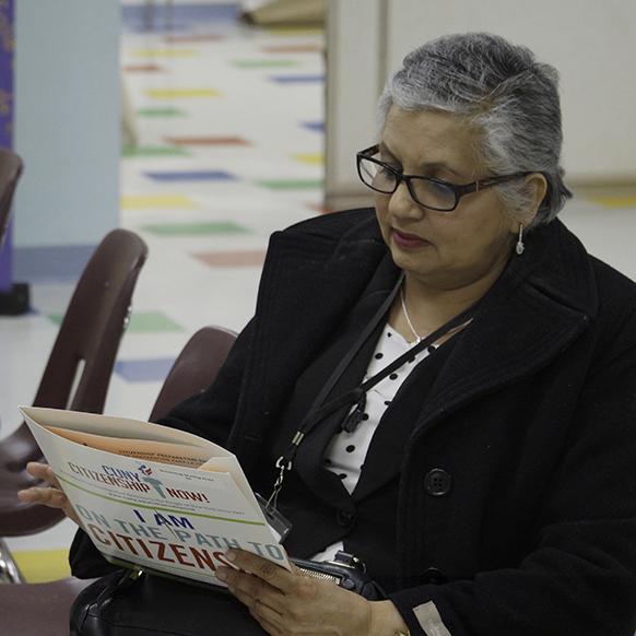 Citizenship event participant reading folder