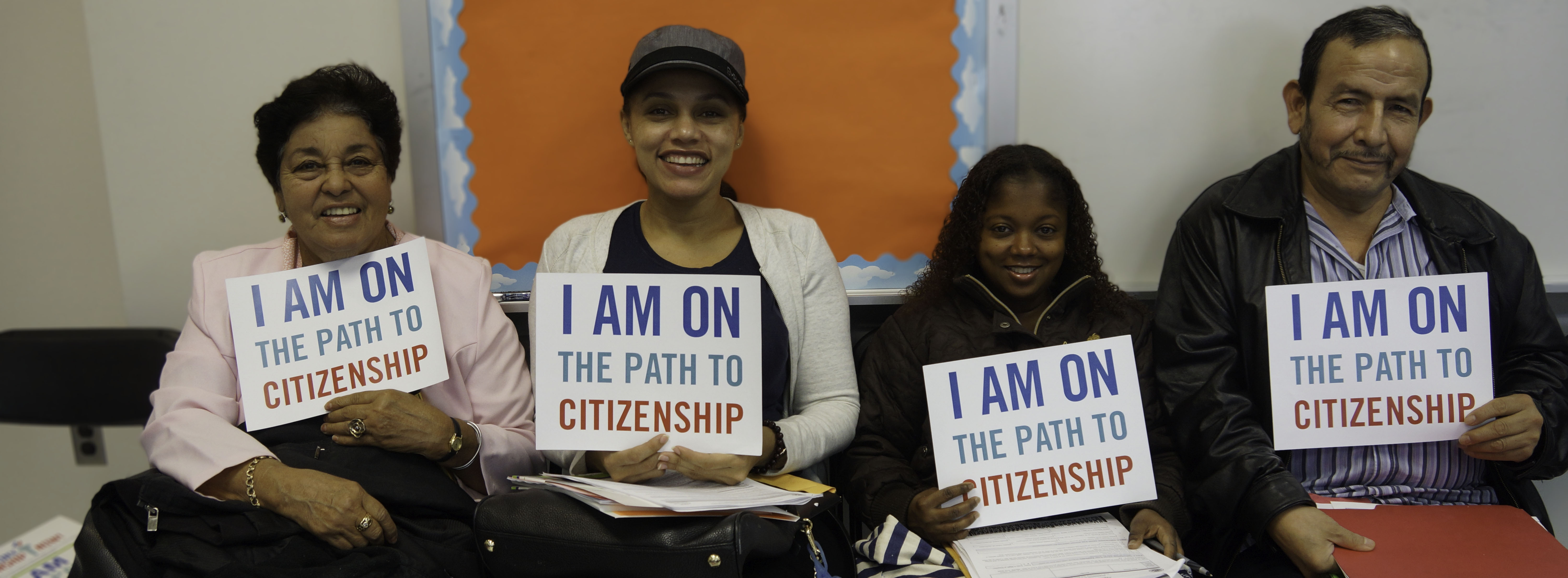 "Four people, three females and one male, sitting next to each other hold signs that say ""I am on the path to citizenship"""
