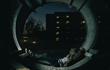 Young person sleeps on concrete outside in the dark