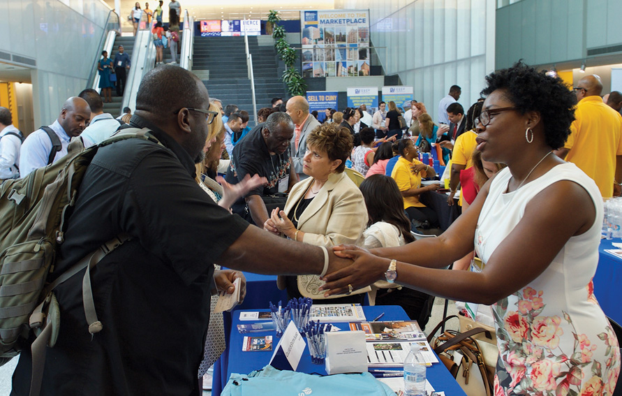 Dhaydia Smith, a purchasing agent at the College of Staten Island, greets attendees at the MWBE conference.
