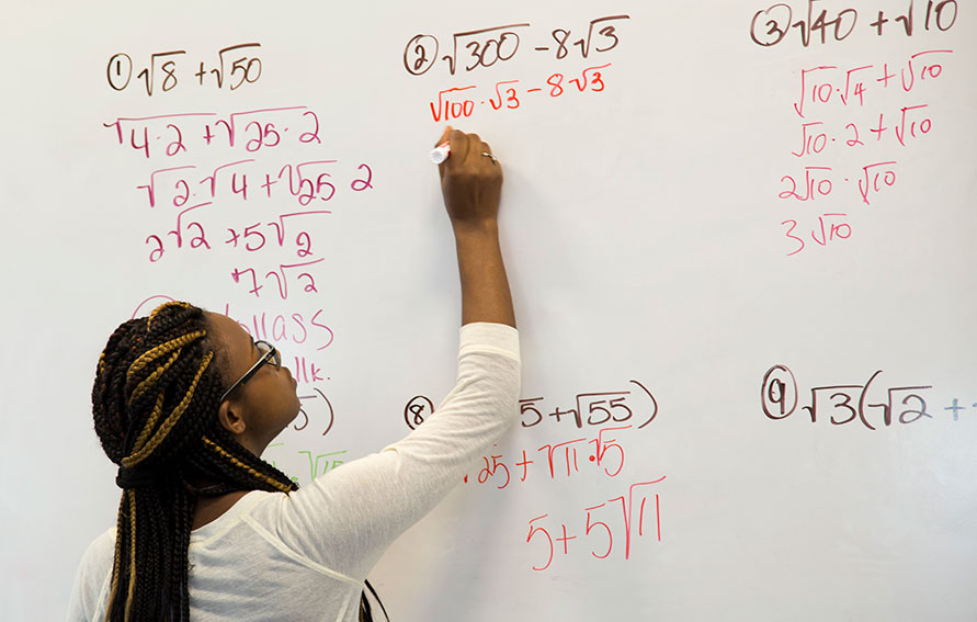 student working on math problem at white board